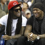 New Orleans rapper Lil Wayne sits with Birdman during the New Orleans Hornets NBA basketball game against the Miami Heat in New Orleans
